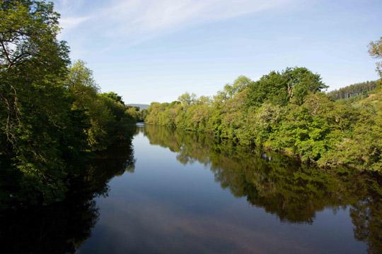 Flat calm river looking westward from the bridge