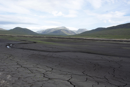 Dry cracked loch basin, with faint tinge of green where new grass is sprouting