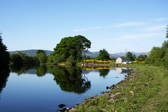 Peaceful scene looking across calm water towards the hydro scheme
