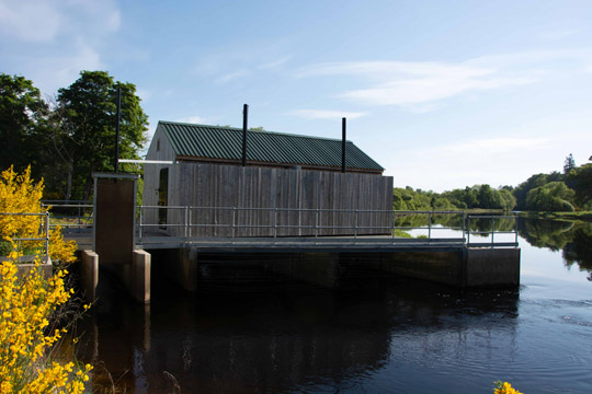 The front of the wooden building housing the hydro scheme, with the water running under the building
