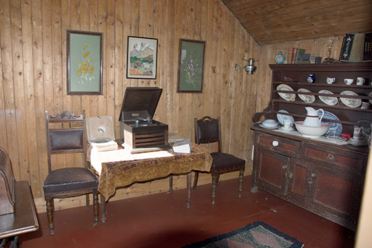 1930s wooden panelled best room of the Tin cottage. With a small table, record player and 2 chairs with a wooden dresser on the right