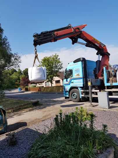 Lorry delivering a tonne bag of gravel - bag several feet of the ground