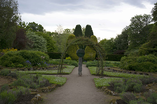 The central archway in the formal gardens with a architectural sculpture under the arch