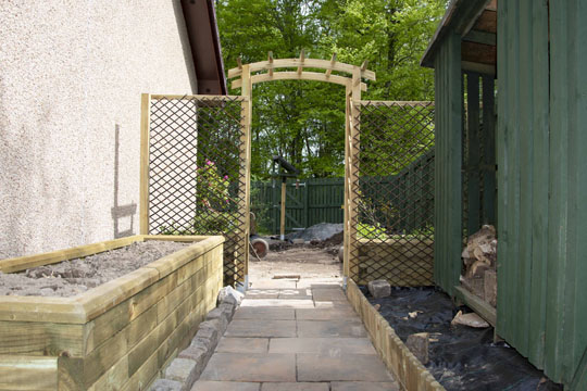 Raised bed on left, path freshly slabbed, arch and trellises installed