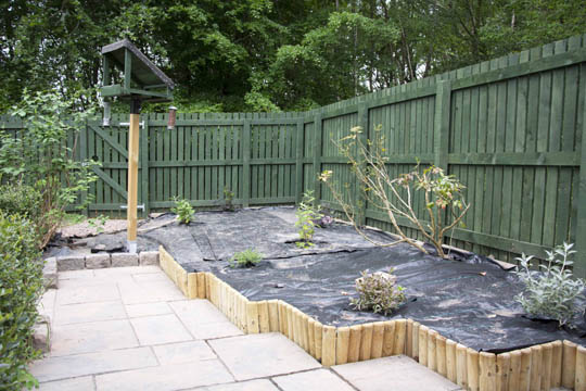 Sladded patio, wooden edging, raised bed with membrane and plants