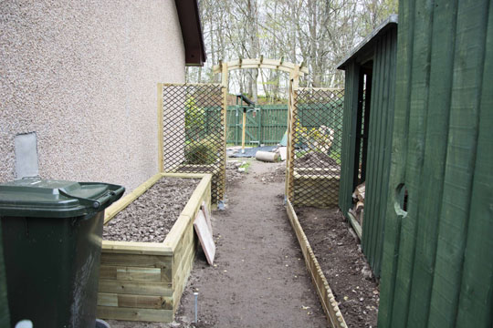 wheelie bin and raised bed on left, gate and woodshed on right. Soil path in the middle. Looking at arch and 2 more raised beds
