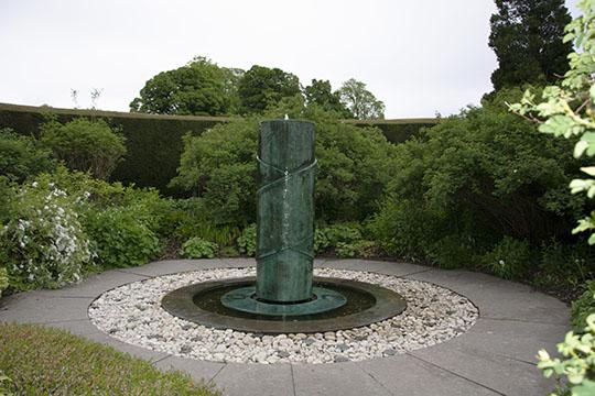A tall water feature within a secret garden