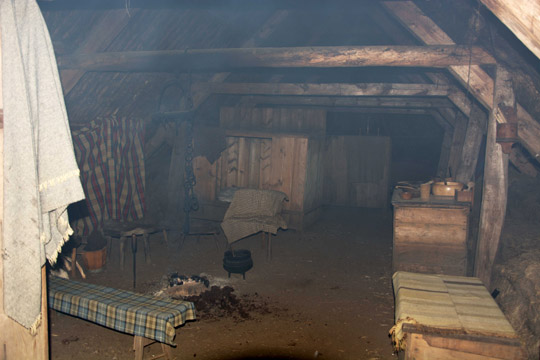 Inside one of the cottages, it is very smoky with a fire in the centre of a soil floor