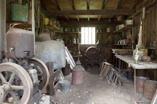 Inside the lower level of the woodworkers shed, with benches and tools