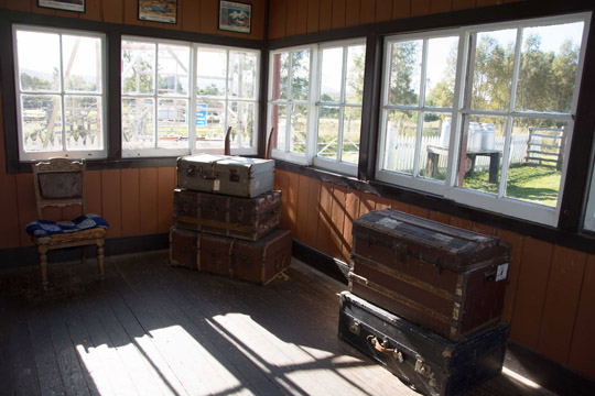 Inside the railway waiting room with trunks stacked and a wooden chair