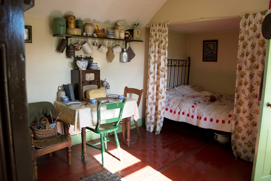 Inside the Tin Cottage, a bed in the corner with curtains round it, a small table and chairs