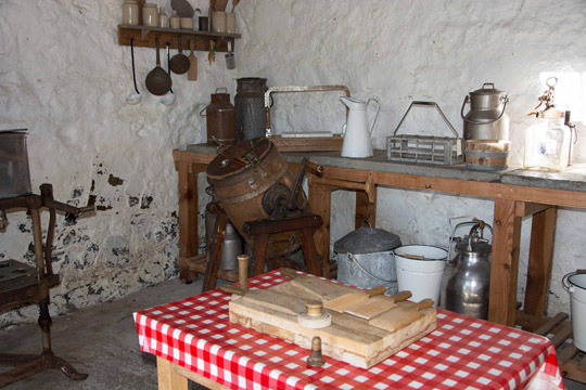 Inside the dairy with a red and white covered table with clappers on it, and in the background a milk churn