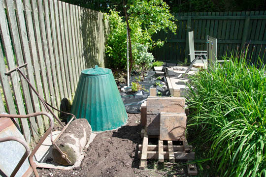 area with old compost bin, roller, and old slabs