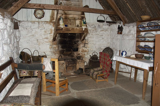 inside the old cottage, flagstone floor and white washed walls very basic chairs and a bench - all wooden