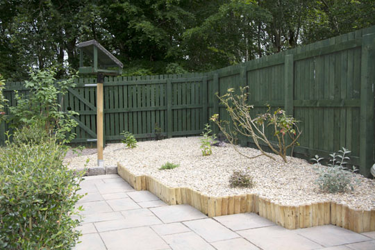 Slabbed area then wood edging, raised gravel bed and small plants
