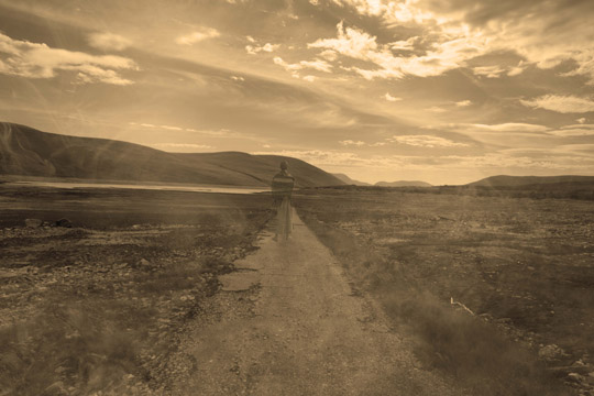 sepia coloured photo of old road and faded woman on path