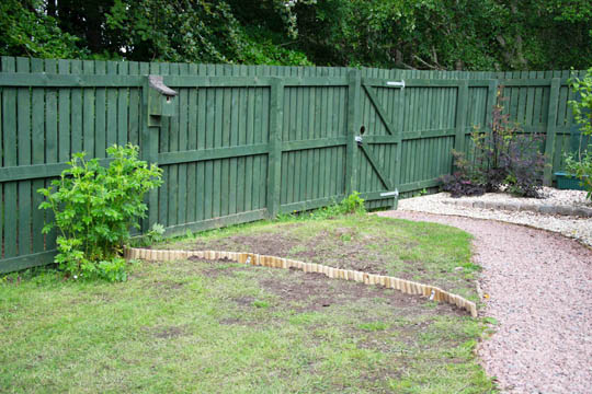 area beside gate, lawn now split with wooden edging, closest area is lawn, furthest area another wildflower area