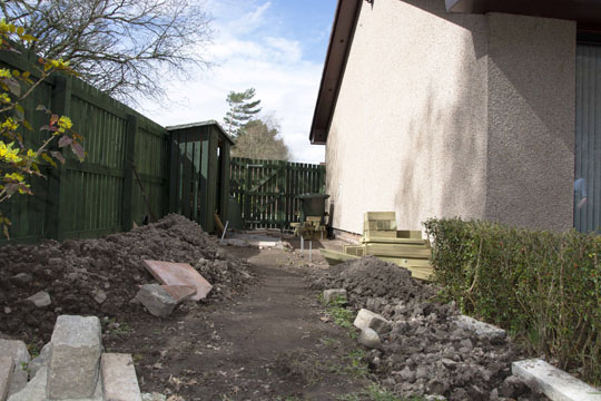 Gable end of house on right, bare ground with lots of soil mounds