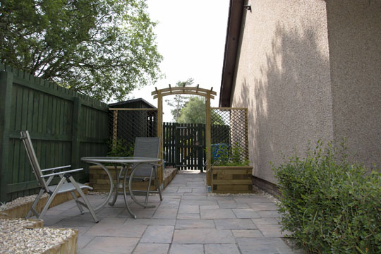 Looking towards the front, table and chair on left arch and 2 planters mid screen and gate in background