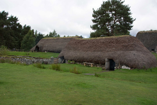 Two township buildings will very short walls and thatched rooves that nearly reach the ground